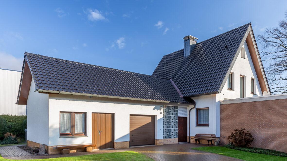 Einfamilienhaus mit Satteldach und Flachdachziegel J13v in vulkanschwarz matt