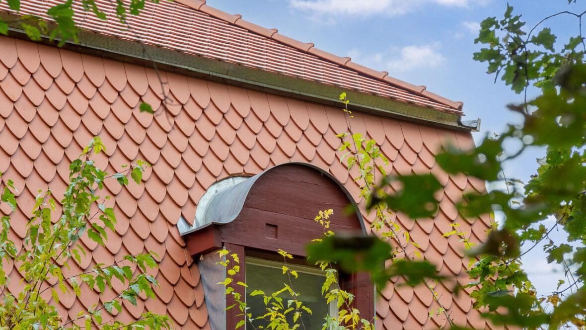 Ein einzigartiges Mansarddach mit gotischem Biber und Turmbiber in naturrot gedeckt.